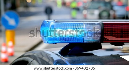 blue flashing police car during a roadblock to hunt down the escaped prisoners - stock photo