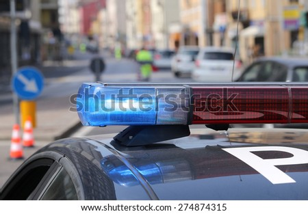 Blue flashing sirens of police car during the roadblock in the city