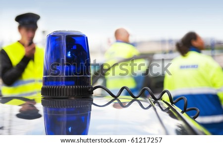 Blue flashlight on top of an unmarked police car, with a team of emergency medical service personnel in the background