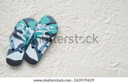 Blue flip flop shoes and on a white sand beach - stock photo