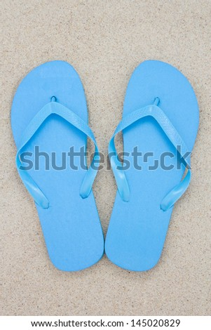 blue flip flops on a sandy beach