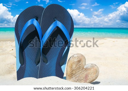 Blue flops and a wooden heart with copy space on the sunny beach - stock photo