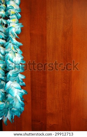 Blue floral hawaiian lei isolated on wooden background - stock photo
