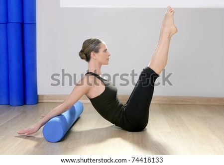 blue foam roller pilates woman sport gym fitness yoga wood floor - stock photo