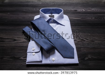 Blue folded shirt and blue necktie on black wooden table. Close up photo with perspective distortion - stock photo