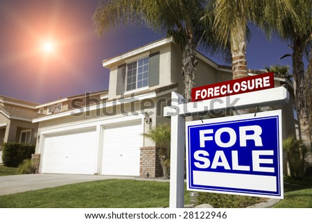 Blue Foreclosure For Sale Real Estate Sign in Front of House with Red Star-burst in Sky. - stock photo