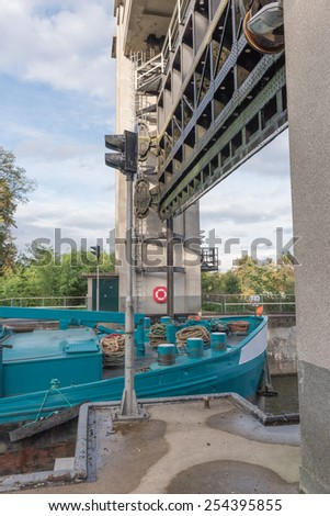 Blue freighter ship leaves gate of lock Bosscheveld build in 1930 in Maastricht, The Netherlands. - stock photo