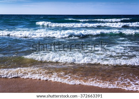 Blue Fresh Water Whitecap Waves Wash Ashore onto a Sandy Beach. Rhythm of Nature. Bright Clear Day. Seashore Background with Copy Space. - stock photo