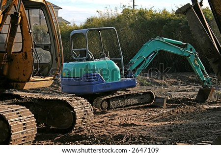 Blue Front End Loader on a muddy job site - stock photo
