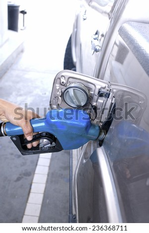 Blue fuel nozzle in pouring to car. - stock photo