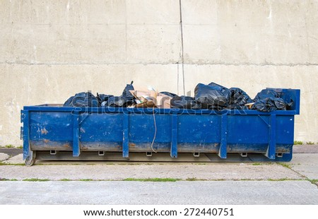 Blue garbage container on the road. - stock photo