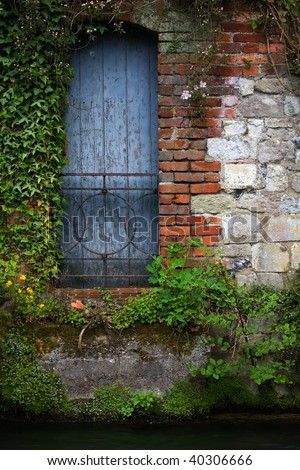 Blue garden door with old stonework and metal gate - stock photo
