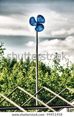 blue garden windmill against cloudy sky at summer day - stock photo