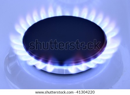 Blue gas flame on hob and space for text on left - stock photo