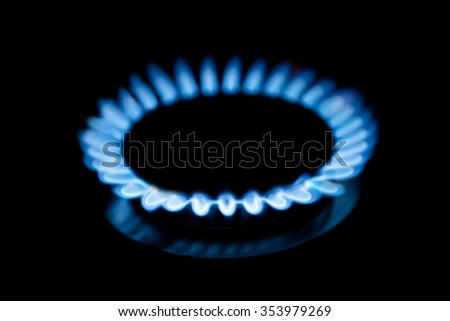Blue gas stove flame in the dark background - stock photo