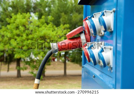 Blue generator outdoors with plugs in outlets - stock photo