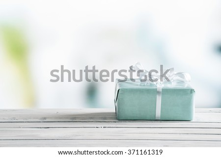 Blue gift box on a wooden table in bright light - stock photo