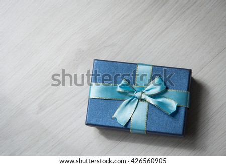 Blue gift box on gray wooden texture background with copyspace for text - stock photo