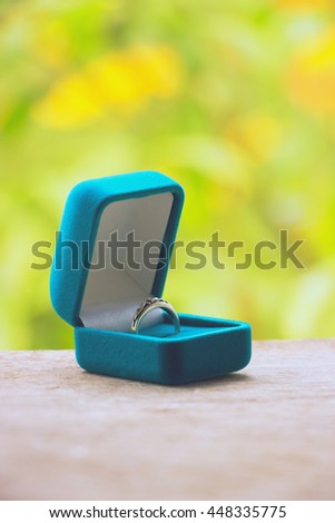 Blue gift box with ring on background of greenery and flowers.Selective focus, toned image, film effect, macro, close-up