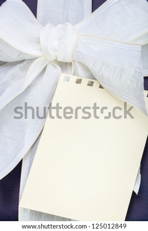 Blue gift box with white ribbon and beige note