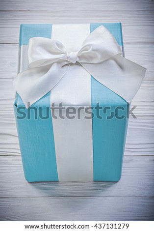 Blue giftbox with white bow on wooden board celebrations concept. - stock photo