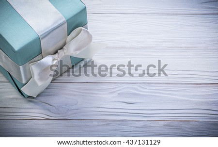 Blue giftbox with white ribbon on wood board copy space celebrations concept. - stock photo