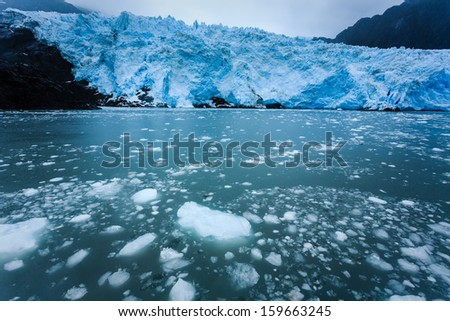 Blue glacier viewed in distance with icebergs and ice chunks in water nearby Alaska - stock photo