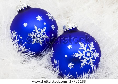 Blue glass ball on white shiny garland making a background, Christmas background