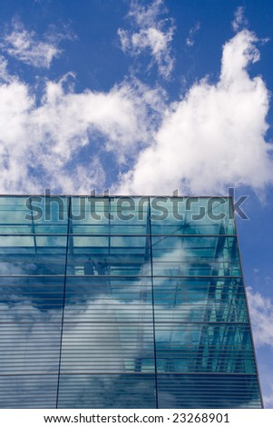 blue, glass building with mirrored sky and clouds - stock photo