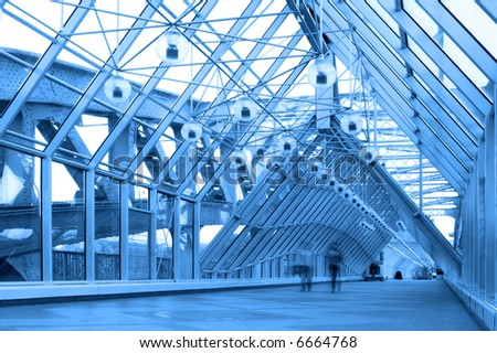 Blue glass corridor in bridge and people walking - stock photo