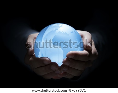 Blue glass earth in human hands - stock photo