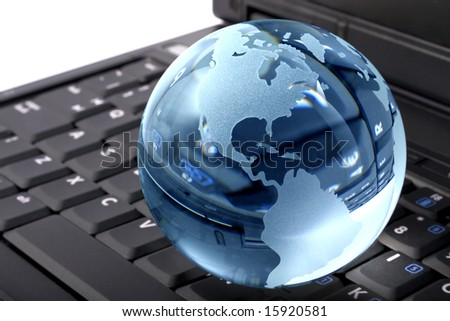 Blue glass globe on a laptop keyboard