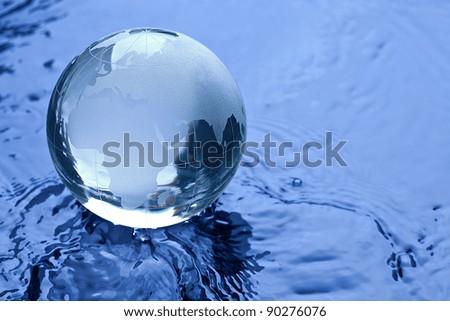 Blue Glass globe on Water - stock photo