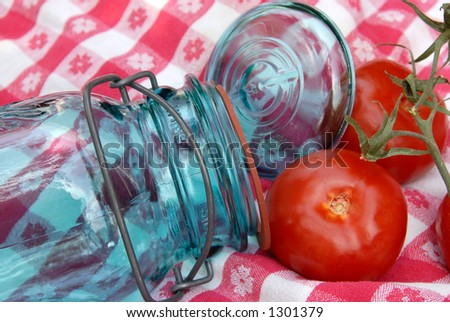 Blue glass jar with a wire holding the lid and rubber ring  onto it, used for canning fruits and vegetables, sitting on  a vintage table cloth with 3 tomatoes. - stock photo