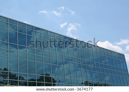 Blue glass office building reflecting the sky with clouds