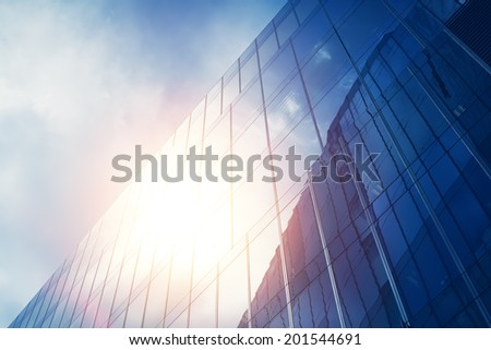 blue glass wall of skyscraper with sun reflection - stock photo