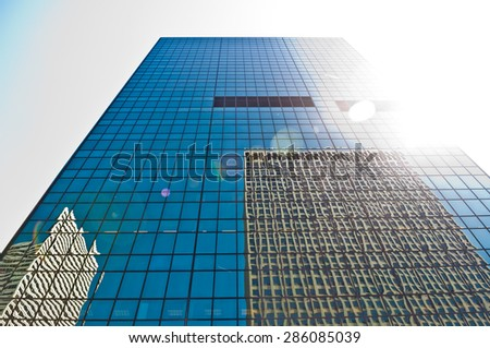 Blue glass window facade of a high-rise building reflecting other skyscrapers on a sunny day - stock photo