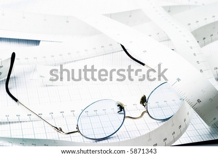 Blue glasses on measuring tape and graph paper