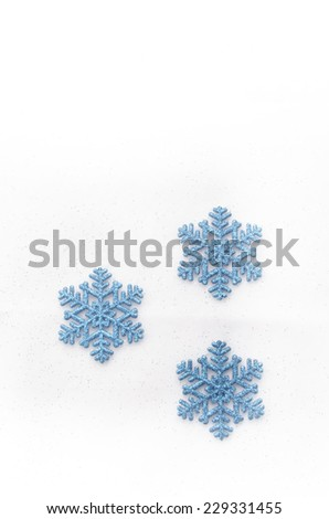blue glittering snow flakes on bright background - stock photo