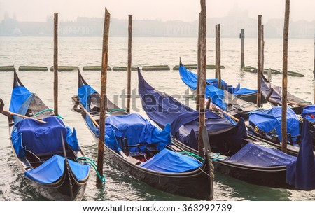 Blue gondolas moored by San Marco quay at windy winter day in Venice - stock photo