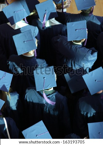 blue graduation caps from above - stock photo