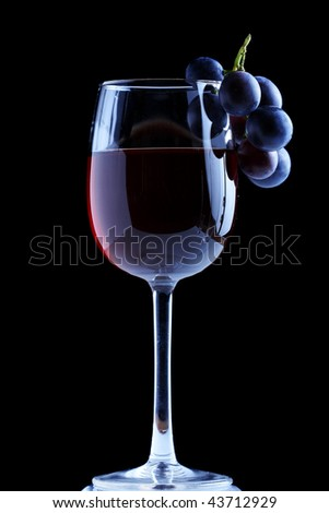 Blue grape cluster and red wine, black background - stock photo