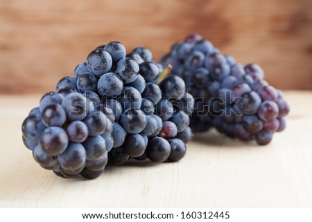 Blue grape clusters on wooden background. Shallow dof