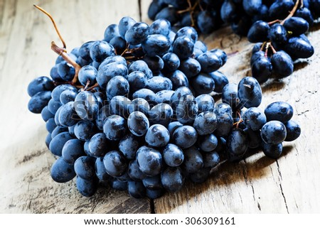 Blue grapes on old wooden background, toned image, selective focus