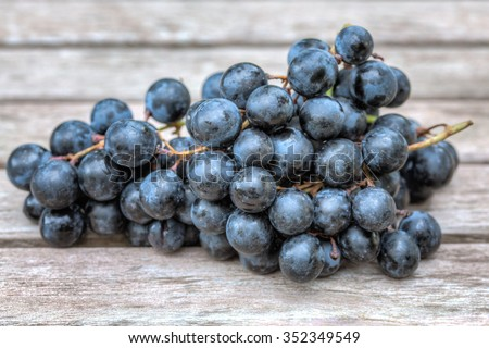Blue Grapes on wooden table.