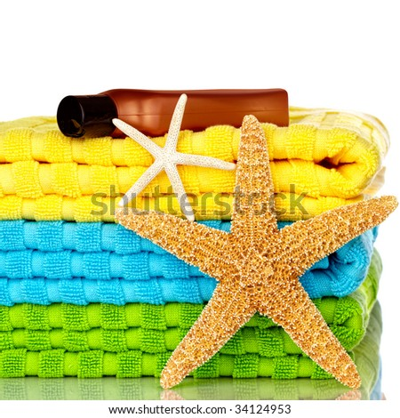 Blue, Green and Yellow Beach Towels With Starfish And Sunscreen Isolated On White Background - stock photo