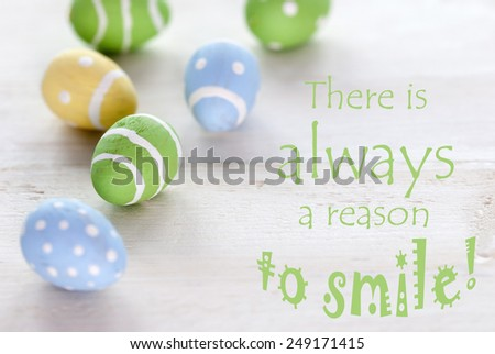 Blue Green And Yellow Easter Eggs Which Are Dotted And Striped On Wooden Vintage Background With English Life Quote There Is Always A Reason To Smile For Easter Greetings - stock photo