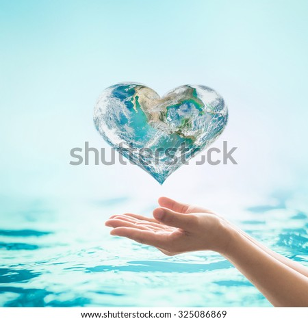 Blue green heart shape planet with turquoise cyan color wavy water background over beautiful woman human hands: World water environmental health concept: Elements of this image furnished by NASA  - stock photo