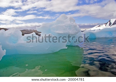 Blue green iceberg with snow covered mountains - stock photo