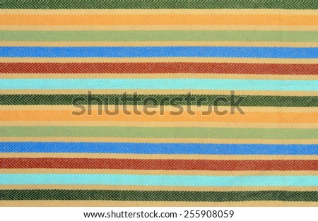 Blue, green,red colors stripes on fabric as a background. Color stripe wool scarf.